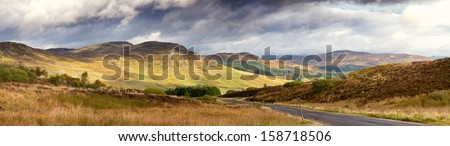 Dramatic sky over the glen with road running through. Scottish Highlands, UK - stock photo