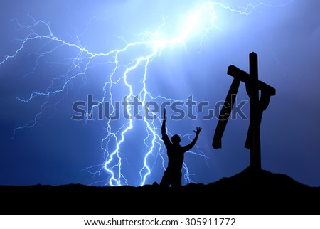 Dramatic sky scenery with a mountain cross and a worshiper - stock photo