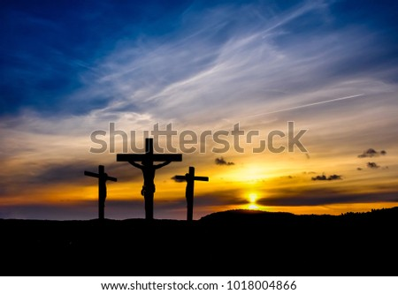 Dramatic sky silhouettes three crosses
