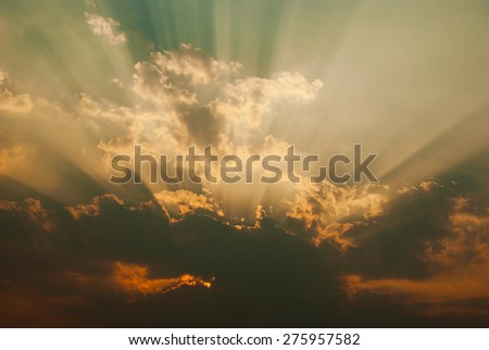 Dramatic sky with sunbeams before sunset - stock photo