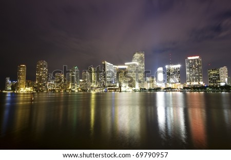 Dramatic skyline of downtown Miami and Biscayne Bay at night time - stock photo