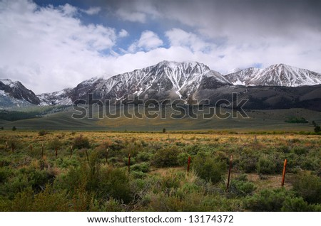Dramatic Spring Meadow and Snow Covered Mountain Scene - stock photo