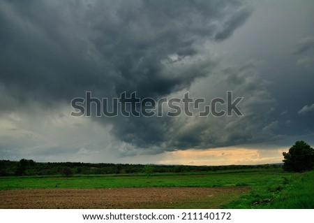 Dramatic storm scene with rain at the horizon and rural path going towards left. - stock photo