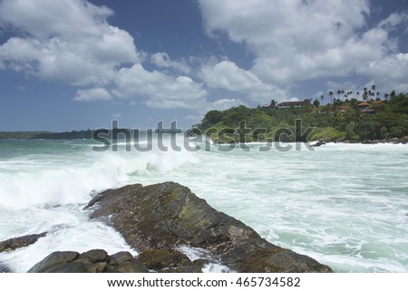 Dramatic storm waves and surf crashing onto a remote tropical beach in south east Sri Lanka near Talala beach and Matara during the south east monsoon period with stormy rain clouds, and rocky beach.