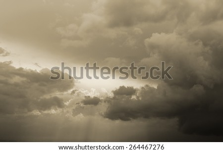 Dramatic stormy sky with black clouds ready to start raining and sun rays coming out of the clouds. - stock photo
