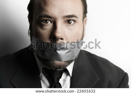 Dramatic stylized close-up of a very businessman with duct tape covering his mouth - stock photo
