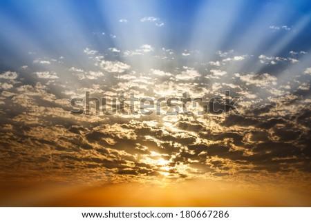 Dramatic Sunbeam  through cloud blue and orange twilight sky background - stock photo