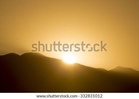 Dramatic sunrise and light rays behind the silhouette of the mountains of Cafayate in Salta Province. Argentina - stock photo