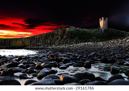 Dramatic sunrise at Dunstanburgh Castle HDR - stock photo