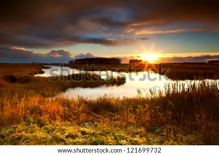 dramatic sunrise over pond close by Leekstermeer, Drenthe, Netherlands - stock photo
