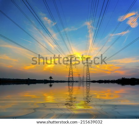 dramatic sunset and blue sky during flood via pylon tower - stock photo