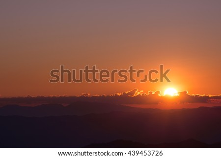 Dramatic sunset and sunrise sky and the sun goes up or down behind silhouette of cloud and mountain layer. - stock photo