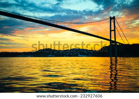 Dramatic sunset cloudy sky above a surface of the sea and long suspension bridge in Bergen, Norway. View from boat - stock photo