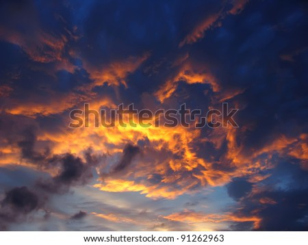 Dramatic sunset like fire in the sky with golden clouds - stock photo