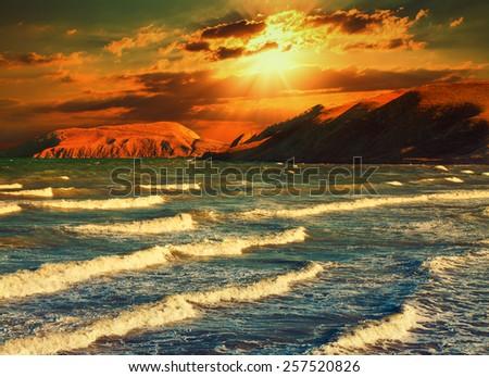 Dramatic sunset over a rocky coast - stock photo