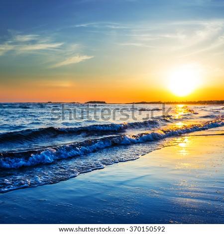 dramatic sunset over a sea coast - stock photo