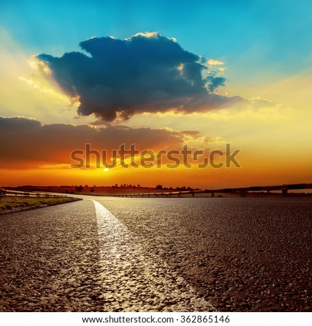 dramatic sunset over asphalt road closeup - stock photo