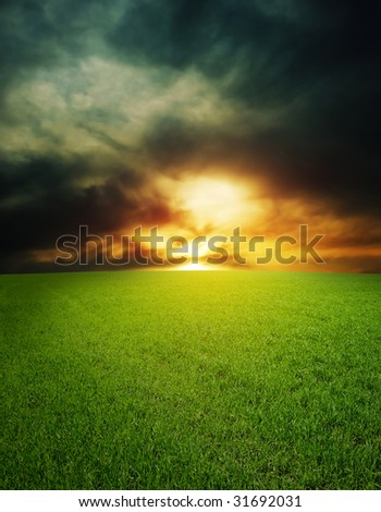 Dramatic sunset over field with green grass