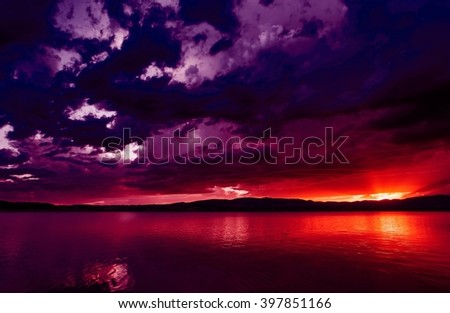 Dramatic sunset over quiet lake in various colors, dreamy look. Natural reflections in water