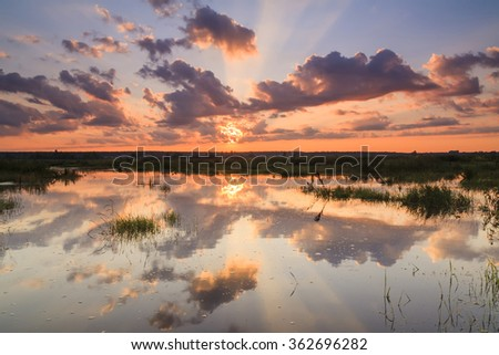 Dramatic sunset over the countryside and the river. - stock photo