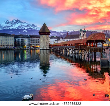 Dramatic sunset over the old town of Lucerne, Chapel Bridge, Water tower and snow covered Pilatus Mountain, Switzerland - stock photo