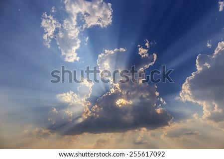 Dramatic sunset rays through a cloudy dark sky - stock photo