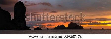 Dramatic sunset rays through a cloudy dark sky and mountains over the ocean - stock photo