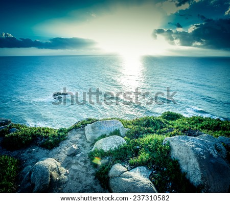 Dramatic sunset rays through a cloudy dark sky over the ocean - stock photo