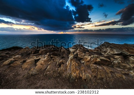 Dramatic sunset rays through a cloudy dark sky over the ocean  - stock photo