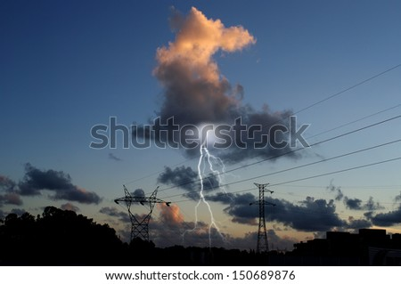 Dramatic sunset view of power distribution station with lightning striking electricity towers. - stock photo