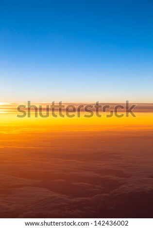 Dramatic sunset. View of sunset above clouds from airplane window - stock photo