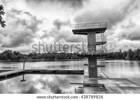 Dramatic view of a concrete springboard against a cloudy sky in an open-air swimming pool in Darmstadt, Germany. - stock photo