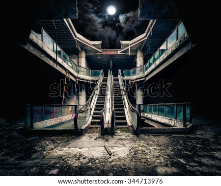 Dramatic view of damaged escalators in abandoned building. Full moon shining on cloudy night sky through collapsed roof. Apocalyptic and evil concept - stock photo