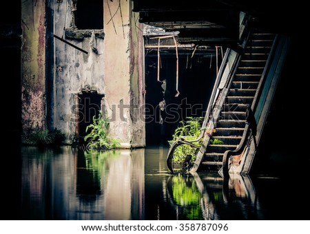Dramatic view of damaged escalators in abandoned shopping mall sunken by rain flood waters. Apocalyptic and evil concept - stock photo