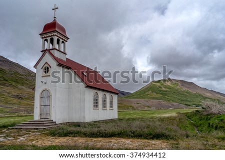 Dramatic view of typical icelandic church next to a mountains.