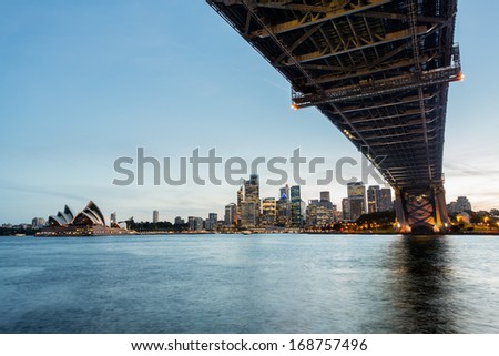 Dramatic widescreen panoramic image of the city of Sydney at sunset bridge in foreground. Includes the Rocks, Bridge, Opera House, and a broad view of CBD and the water in the harbour - stock photo