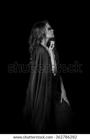 Dramatic woman posing with string of dark beads in her hand and a black cloak around her shoulders in monochrome black and white. - stock photo