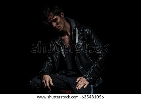dramatic young man in leather jacket sitting and smiling on black studio background