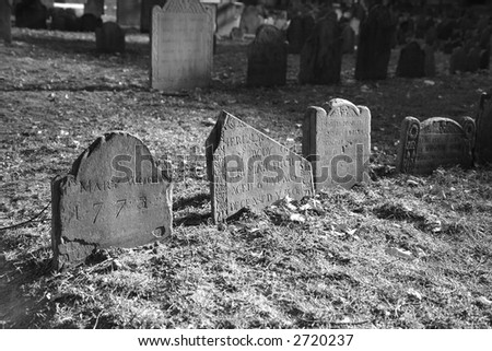 dramatically lit ancient grave stones in black and white in bright sun light on a beautiful winter's day - stock photo