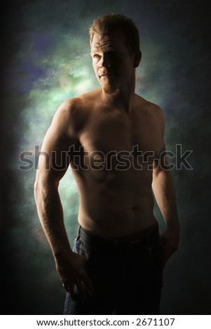 Dramatically lit portrait of shirtless young adult Caucasian man on studio background. - stock photo