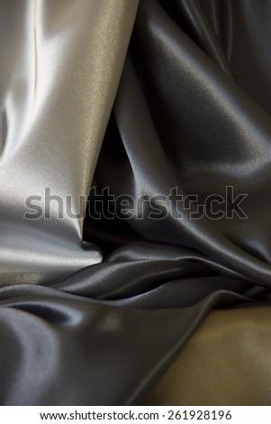 Drape of silver, blue black and field drab silk fabrics - stock photo