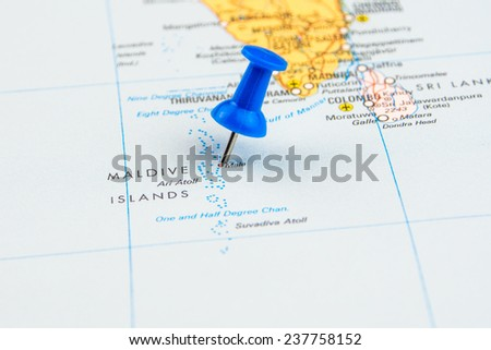 draw-pin stick into real map, identification of final destination, Maldives - stock photo