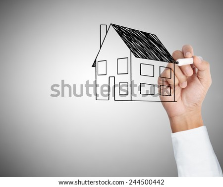 drawing a growing real estate chart. - stock photo
