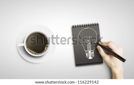 drawing lamp in notepad and cup of coffee