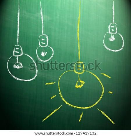 Drawing light bulb on blackboard - stock photo
