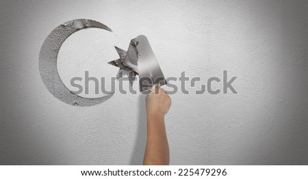 drawing new moon on the wall by using trowel and cement - stock photo