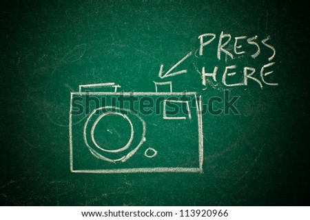 """Drawing of a photo camera on a green chalkboard with an arrow and words """"Press here"""" suggesting the shutter release button. - stock photo"""