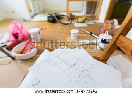 Drawing of home renovation in room full of painting tools - stock photo