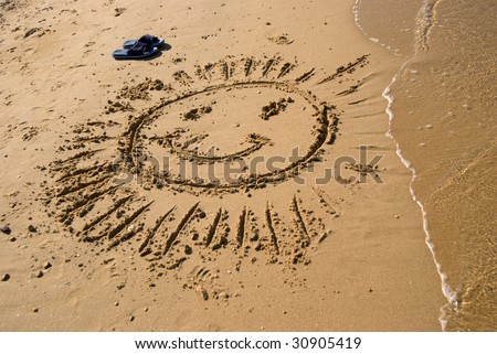 drawing sun on the beach - stock photo