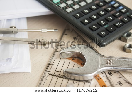 drawing tools with wrench and calculator over wood table - stock photo